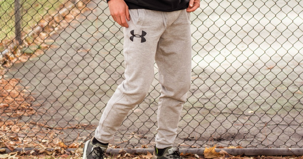 man wearing under armour joggers near fence