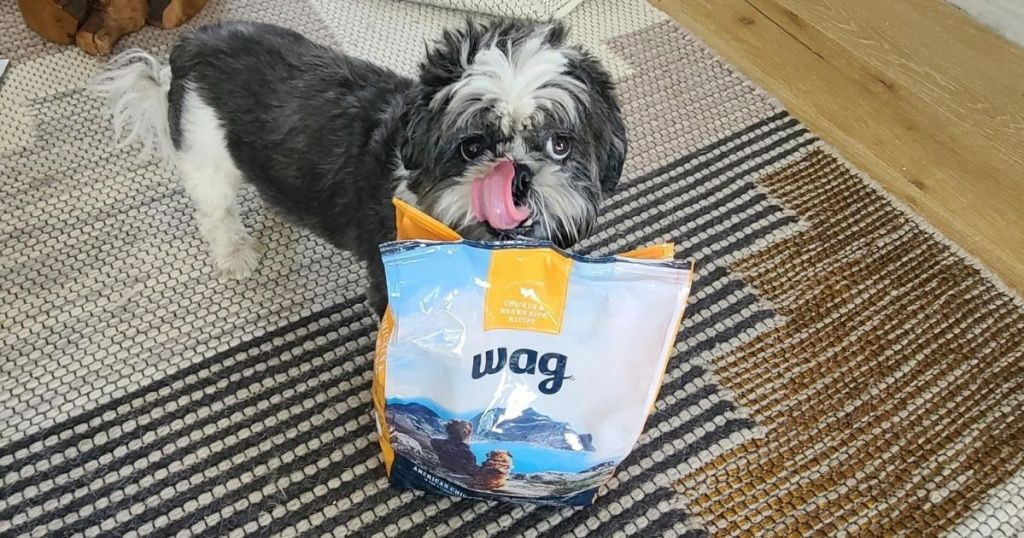 dog licking mouth near bag of dog food