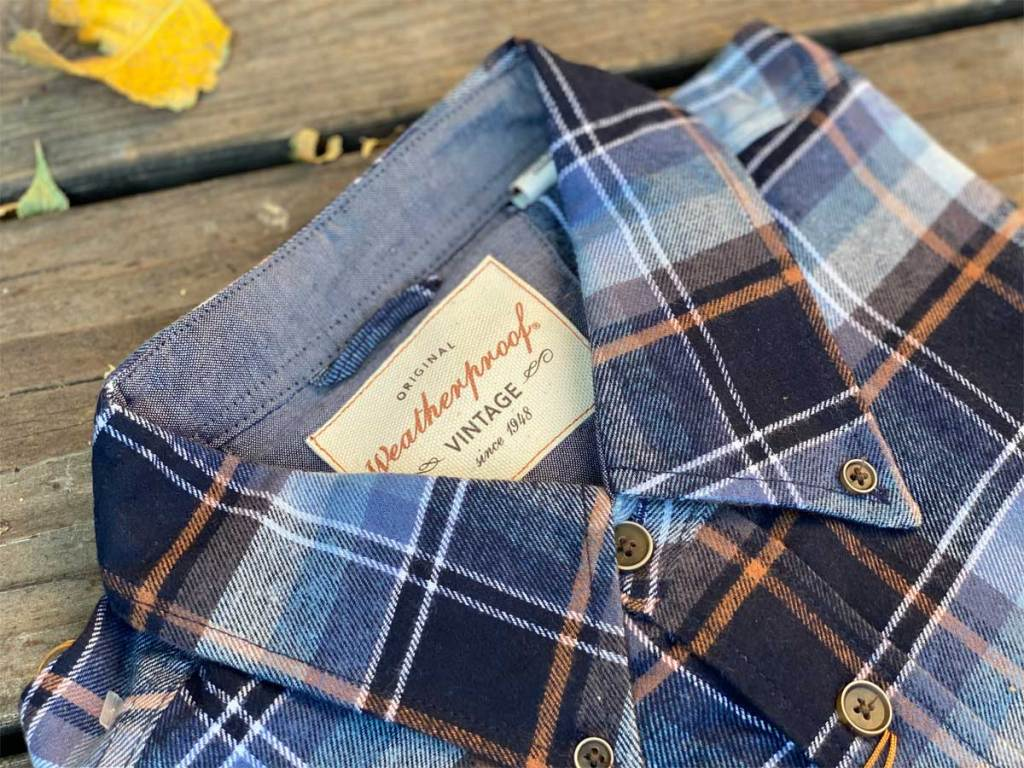 men's flannel shirt folded and on a deck