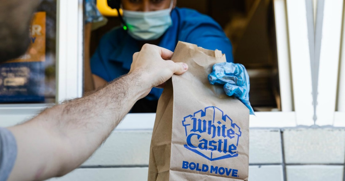 masked and gloved employee handing a man white castle bag at drive thru