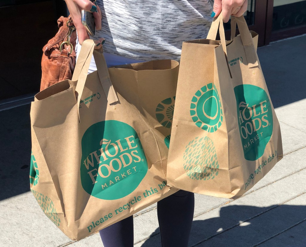 woman holding whole foods bags outside - ways amazon prime day different last year