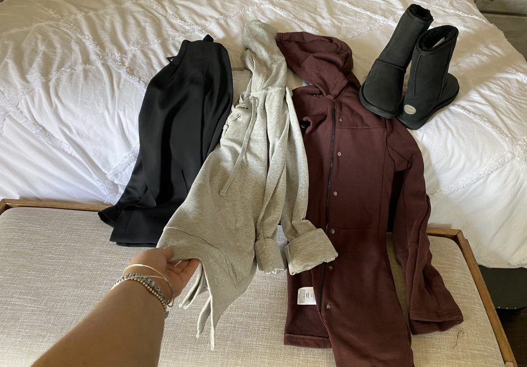 womens clothes and boots on bed