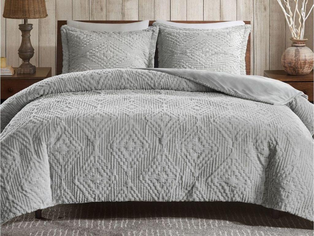 gray comforter on bed in bedroom