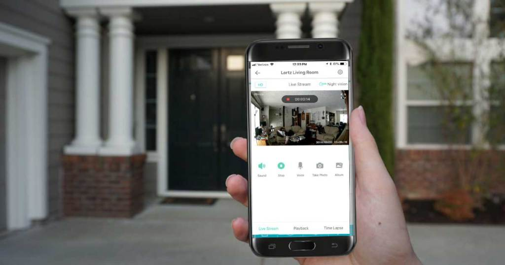 person holding up a smart phone in front of their house showing wyze home security app on phone