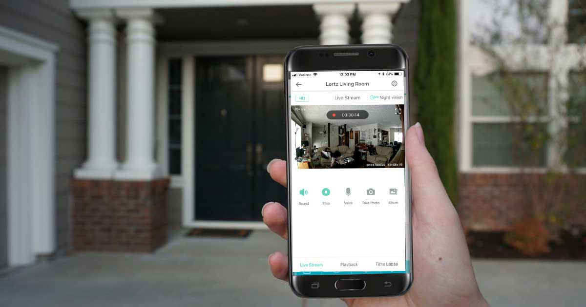 hand holding a phone with a home security app