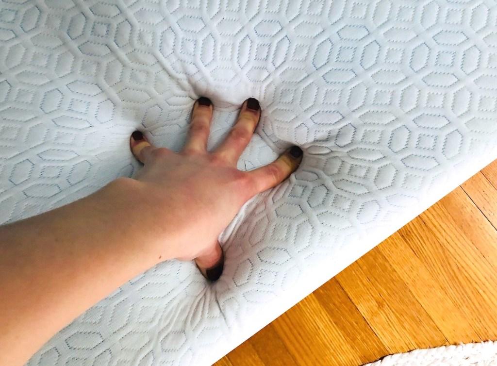 hand pushing down on memory foam mattress