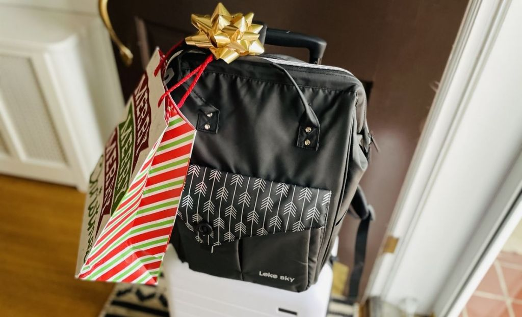 A backpack with a christmas bow and bag on it in front of a door