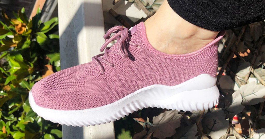 woman's foot with a pink knit walking shoe with white rubber sole