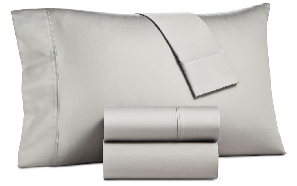 grey sateen pillowcase on a pillow with two folded sheets in front of it