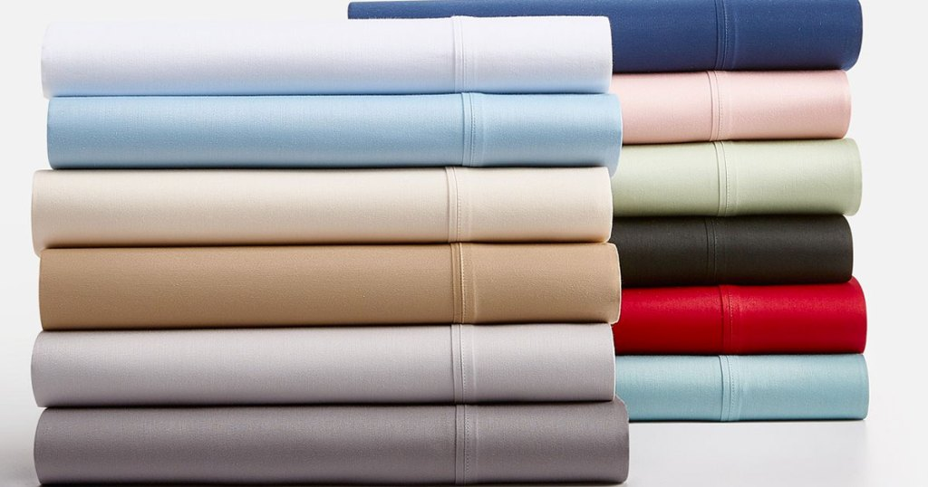 two piles of folded sheets in various solid colors