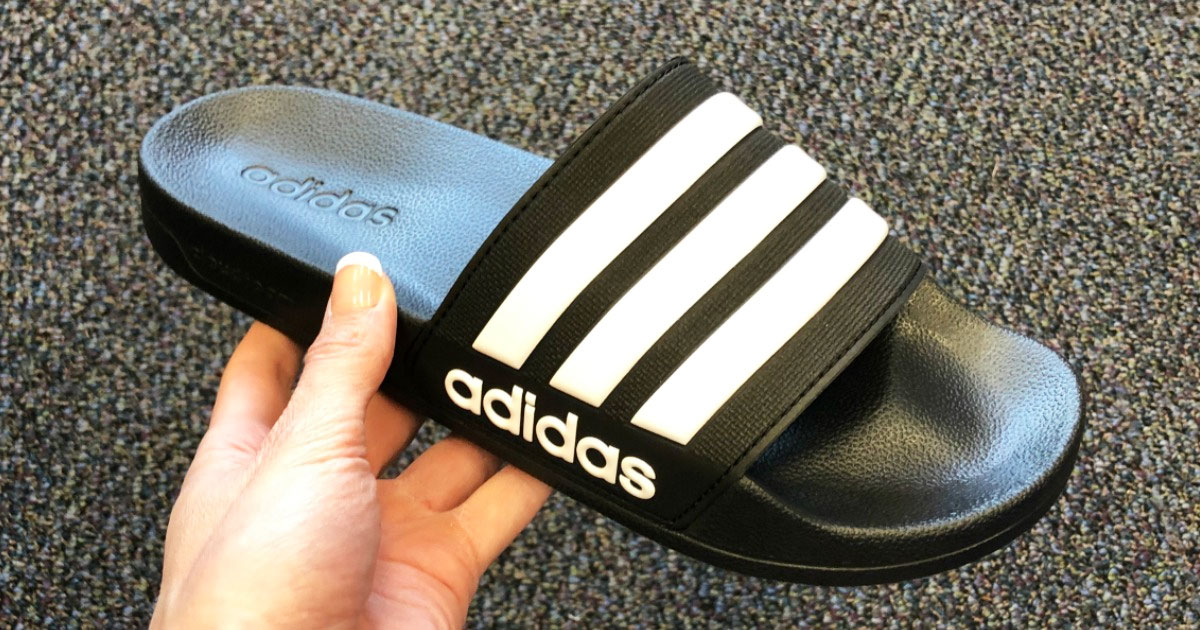 person holding up a black adidas slide sandal with three white stripes across the top