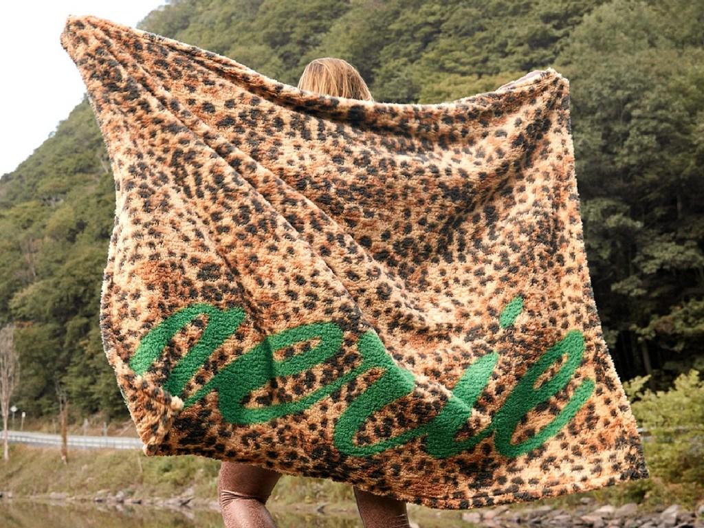 woman outdoors holding animal print blanket