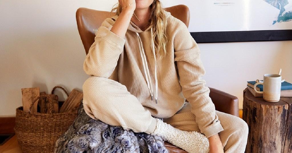 woman in tan hoodie sitting on chair in home
