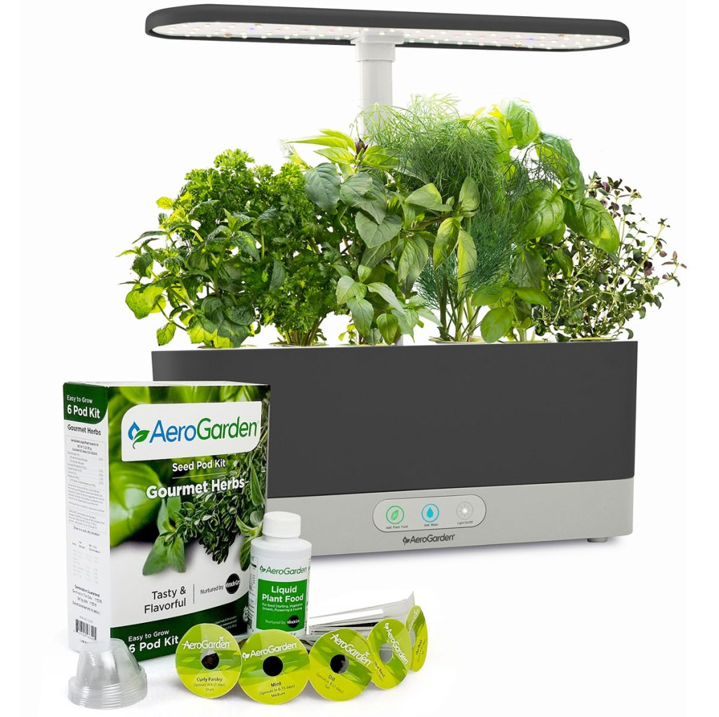 grey indoor garden planter with light on top growing different types of herbs with six seed pods and small bottle of plant food in front