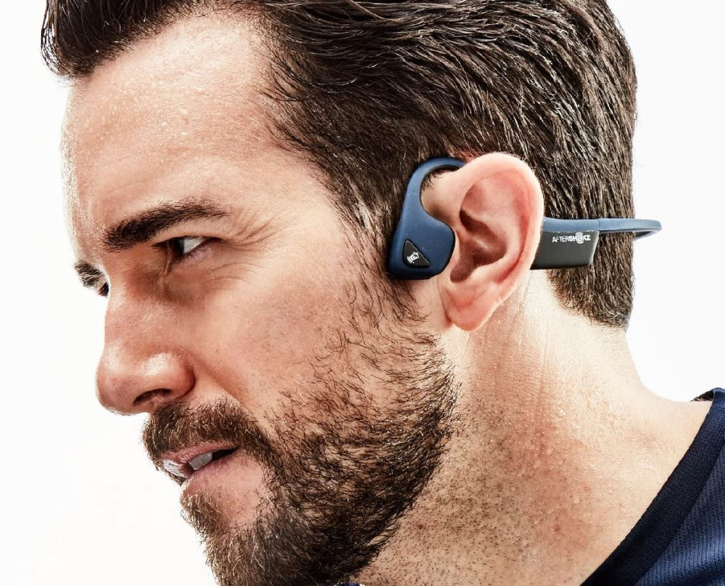 man wearing a set of blue wireless headphones that wrap around the ear