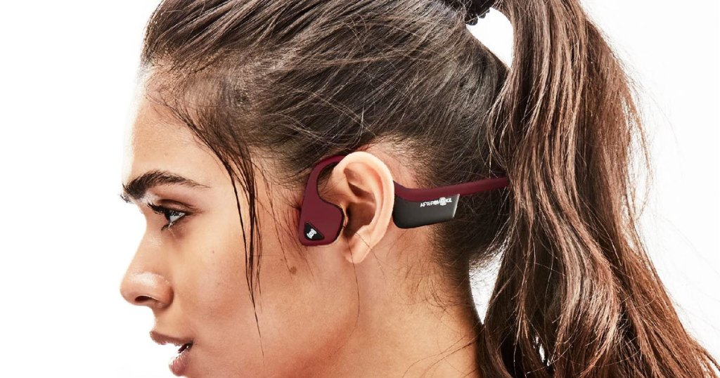 woman with brown hair in pony tail wearing a pair of maroon colored headphones that wrap around the ear