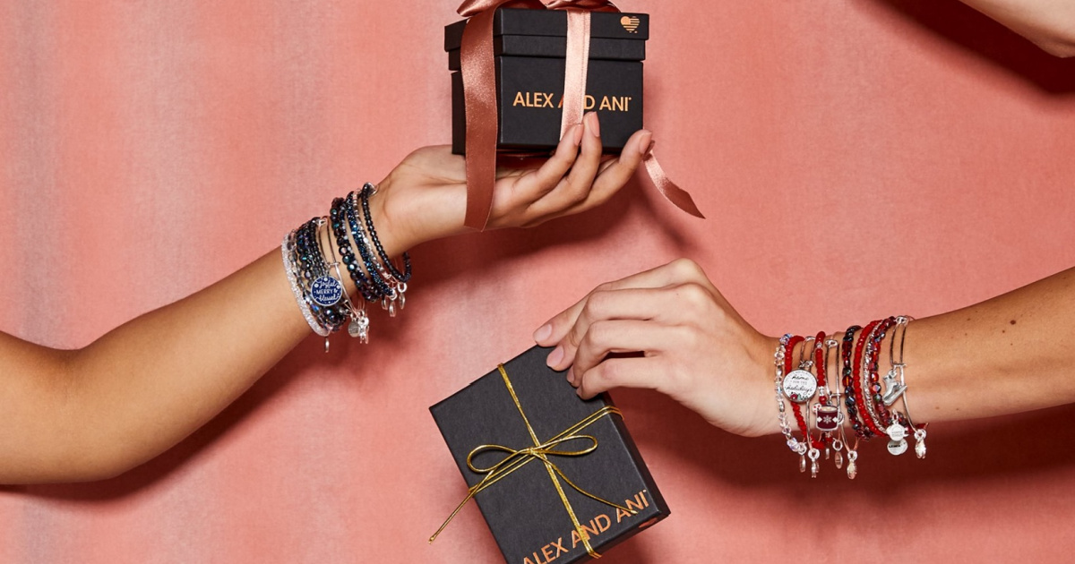 hands holding alex and ani gift boxes with numerous bracelets adorning the wrists