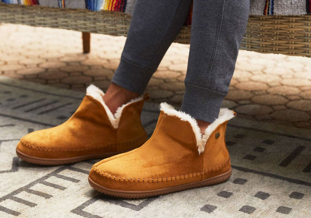 man in grey sweats wearing a pair of tan colored slipper boots