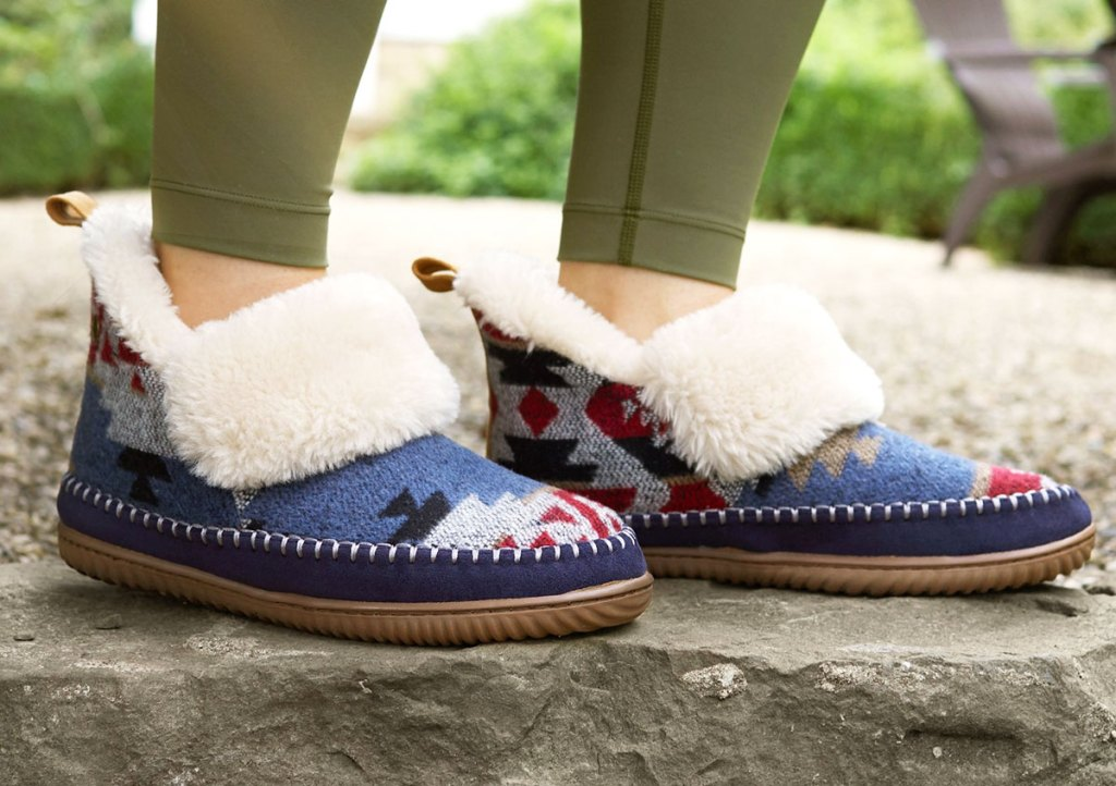 woman in olive green leggings wearing pair of blue print slipper boots with sherpa lining