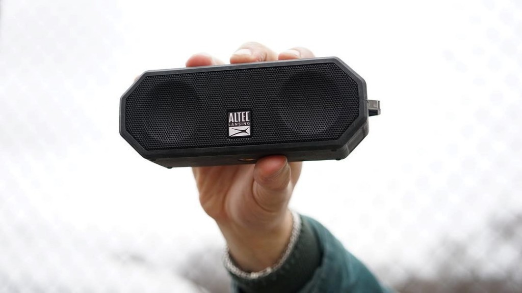 hand holding a small speaker
