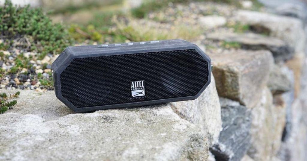 small speaker sitting on a rock wall