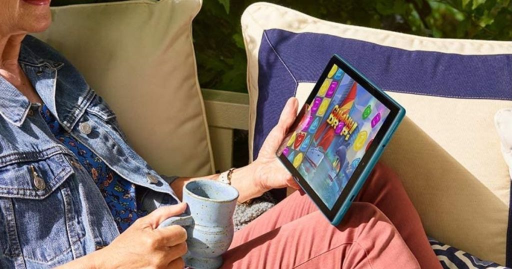 woman reading Amazon Fire HD 10 with a cup of coffee