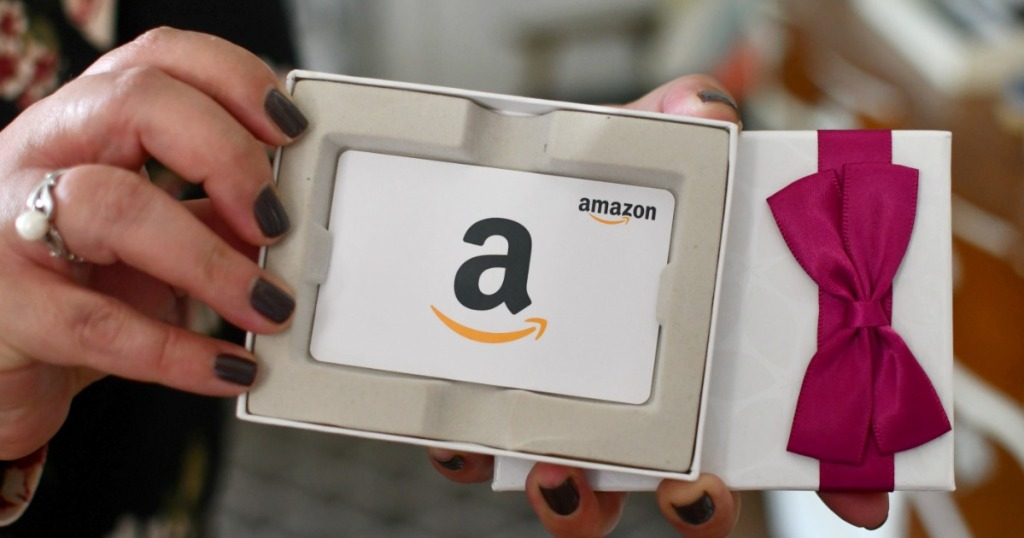 Woman's hand holding an Amazon gift Card