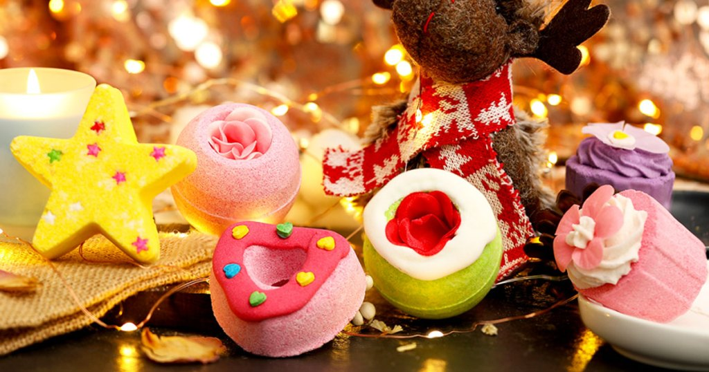 colorful bath bombs in star, heart, and flower shapes near stuffed animal with fairy lights around them