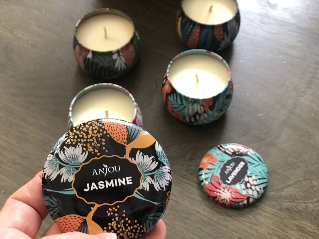 hand holding Anjou Jasmine candle lid with more candles in background