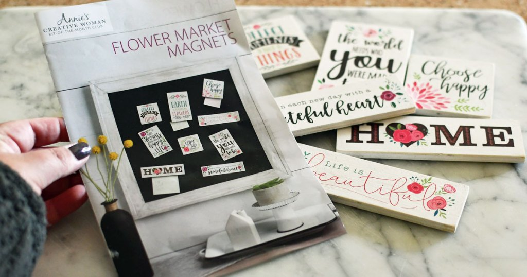 woman holding up farmhouse magnet crafting guide in front of set of magnets