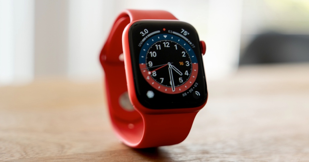red smart watch standing up on table