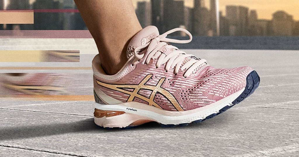 woman running on concrete wearing light pink asics mesh running shoes