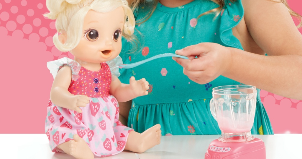 girl feeding baby doll from toy blender