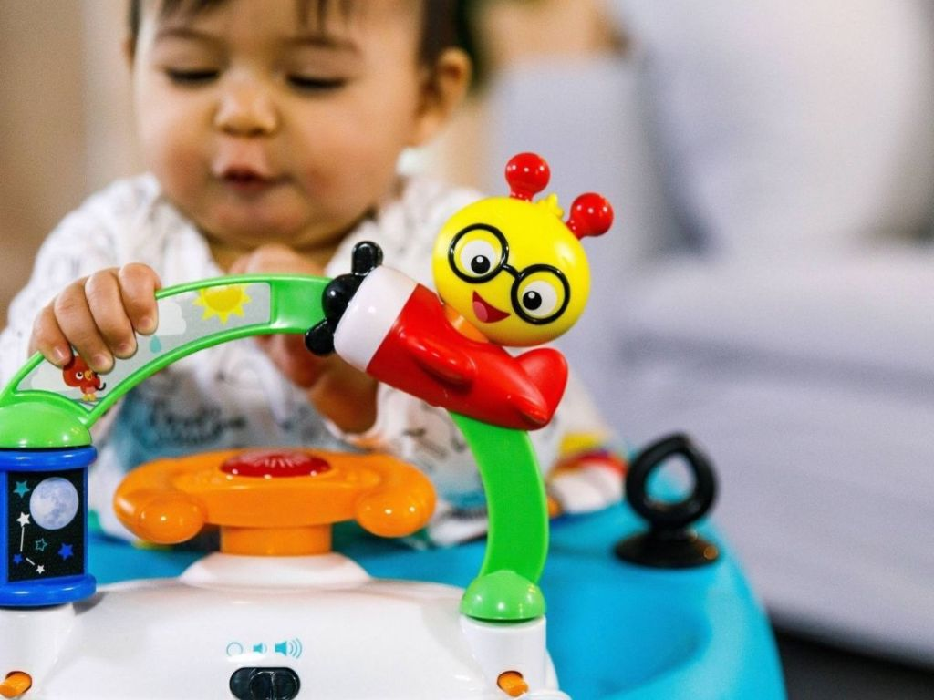 baby in walker playing with toys