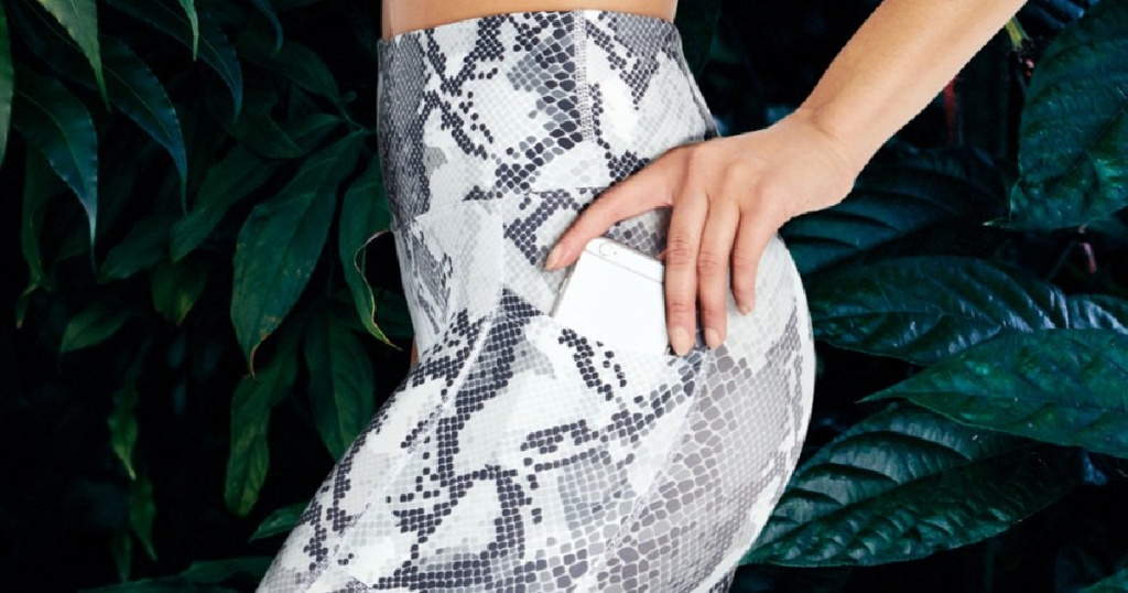 woman in white snake leggings holding phone in side pocket