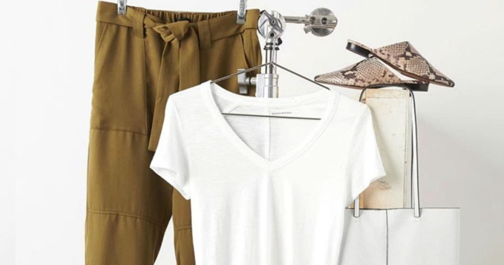 white tee and brown tie-waist pants hanging on a clothing rack with pair of shoes and white bag