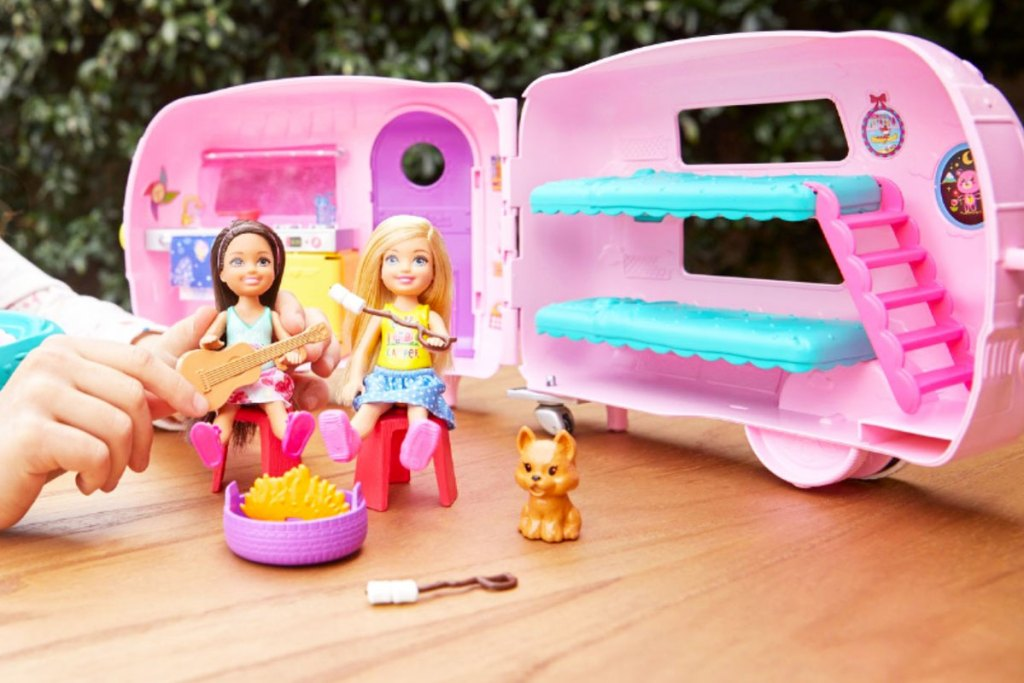 girl playing with pink barbie camper with two dolls sitting by campfire