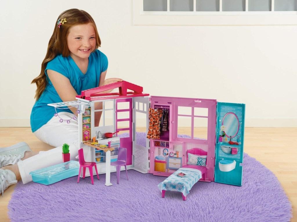 gadis kecil duduk di lantai bermain dengan rumah boneka barbie