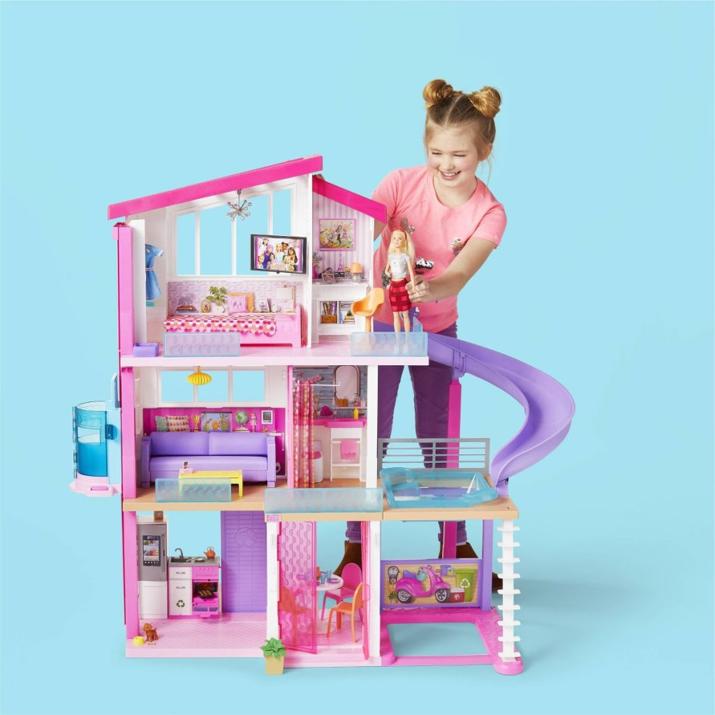 girl standing next to the Barbie Dreamhouse