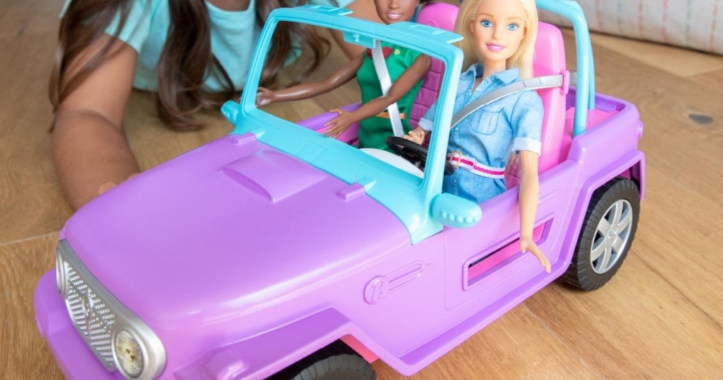 girl playing with purple toy car with two dolls inside