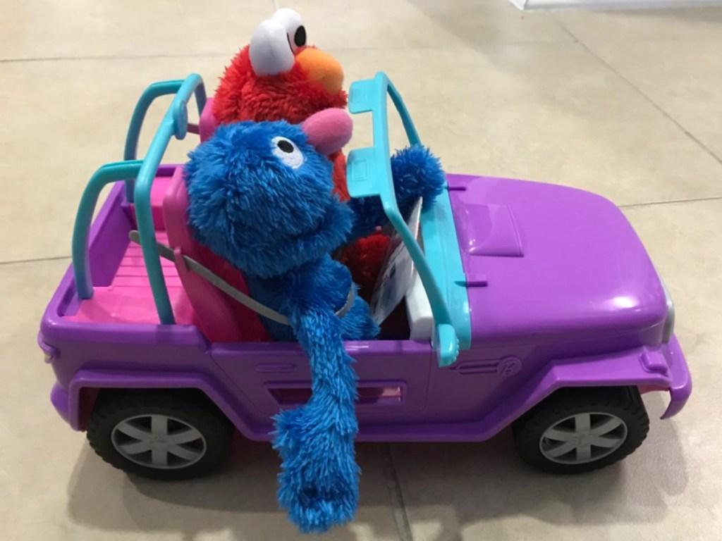 purple toy car with two Elmo stuffed animals