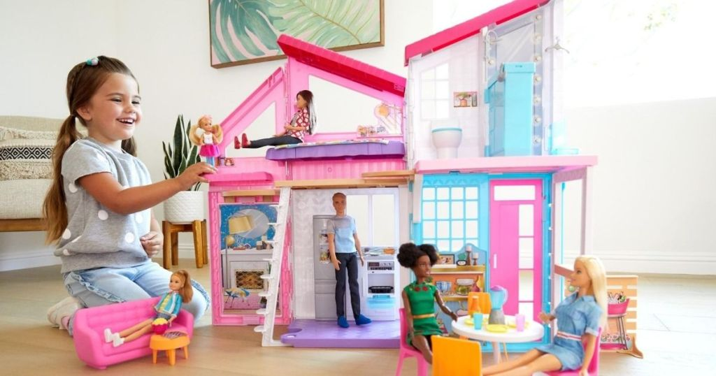 girl playing with Barbie house