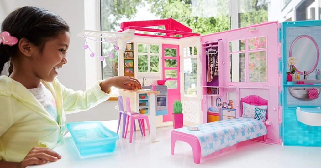 gadis kecil bermain dengan set rumah boneka barbie