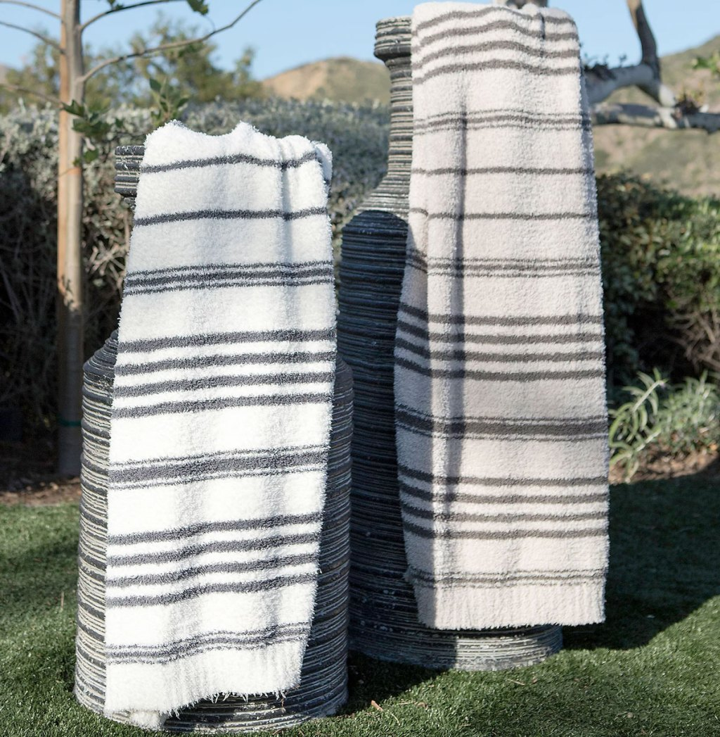 two stiped barefoot dreams blankets draped on large decorative planters outside