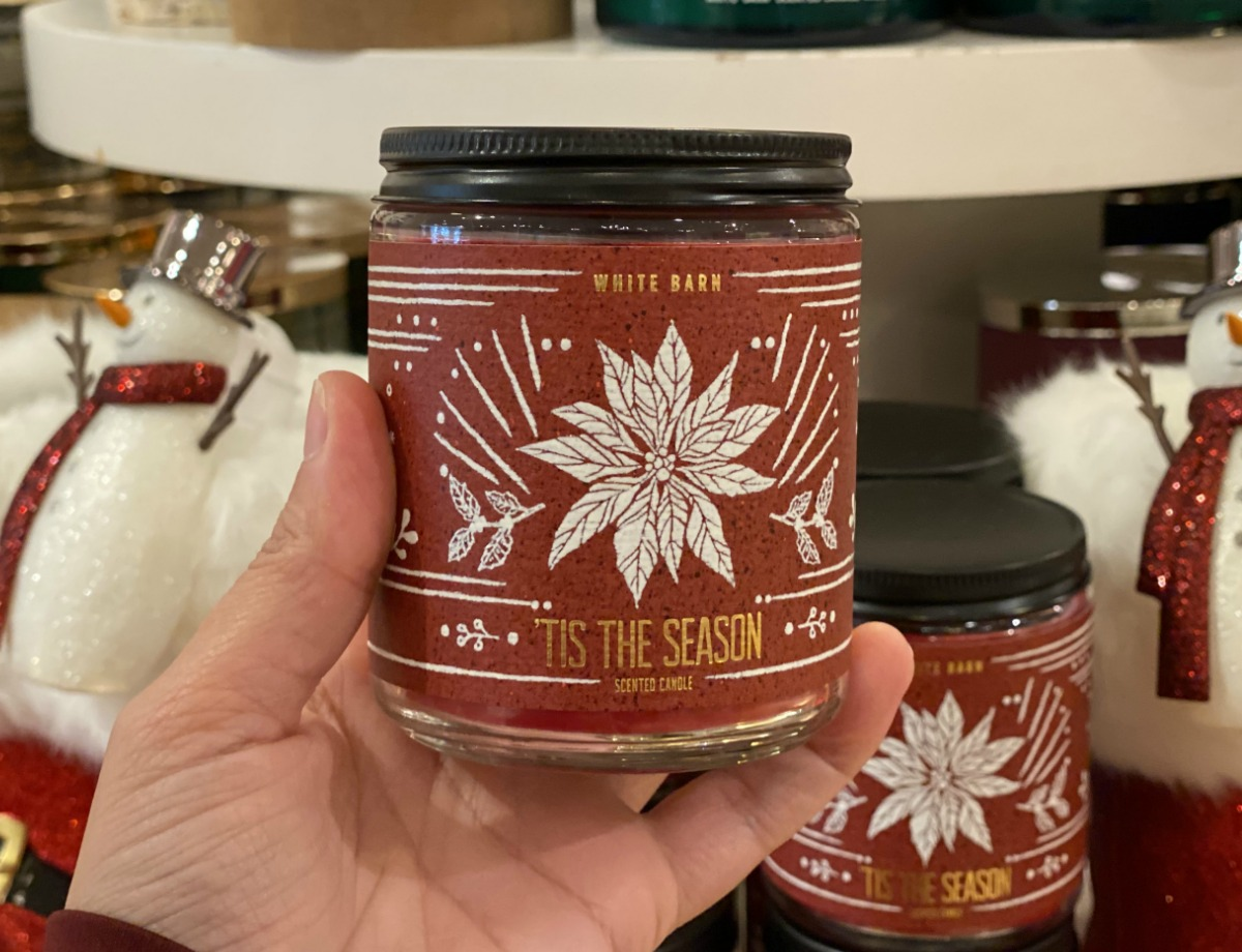 Hand holding a holiday themed single wick candle near in-store display