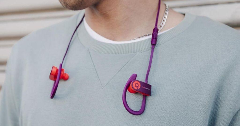 person wearing Beats Powerbeats3 Pop Magenta around their neck