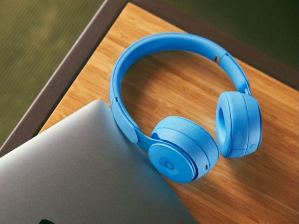 light blue headphones on wood surface