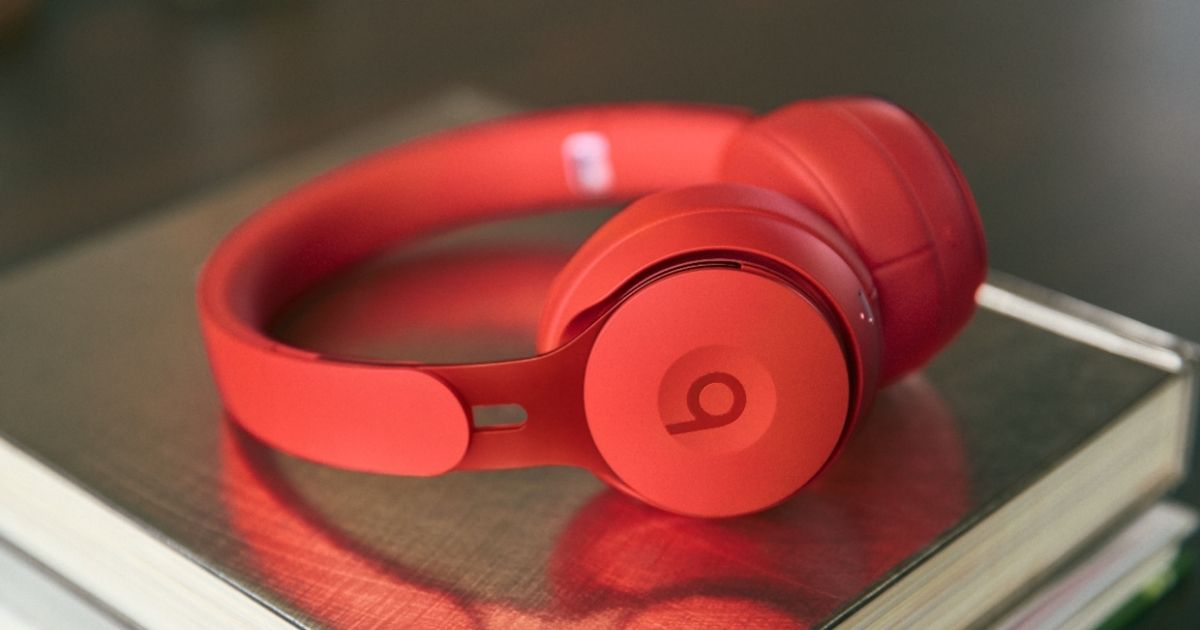 red Beats headphones sitting on pile of books