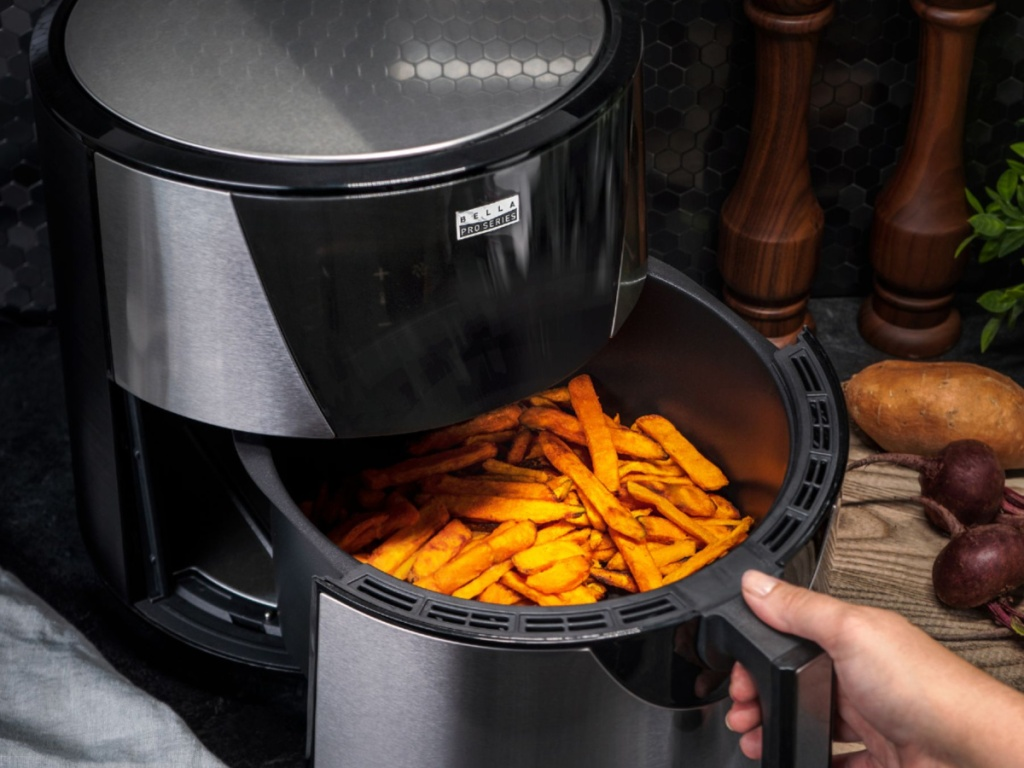 hand pulling out a air fryer drawer filled with air fried food