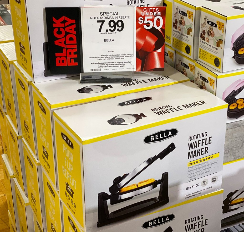 white and yellow boxes of Bella brand rotating waffle makers stacked with macy's $7.99 sale sign on top of them